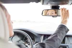 Reflection in rear view mirror of businesswoman driving car